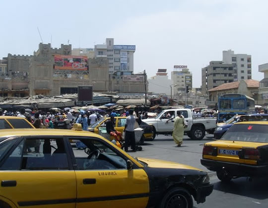 Photo of a busy street scene inlcuding a market and bustling motorway.